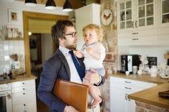 Επιχειρηματίας που έρχεται κατ' οίκον, που κρατά λίγο γιο στα όπλα Στοκ φωτογραφία με δικαίωμα ελεύθερης χρήσης