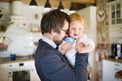Επιχειρηματίας που έρχεται κατ' οίκον, που κρατά λίγο γιο στα όπλα Στοκ Φωτογραφίες