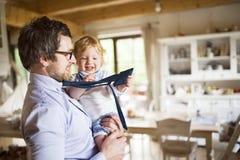 Επιχειρηματίας που έρχεται κατ' οίκον, που κρατά το γιο του υψηλό στα όπλα Στοκ Εικόνες