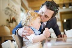 Επιχειρηματίας που έρχεται κατ' οίκον, που φιλά λίγο γιο στο μέτωπο Στοκ Φωτογραφία