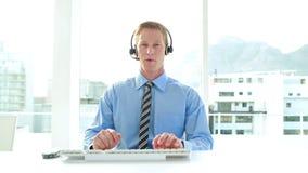 Επιχειρηματίας που έχει ένα τηλεφώνημα με την κάσκα στο τηλεφωνικό κέντρο απόθεμα βίντεο