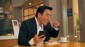 Επιχειρηματίας που έχει τα τρόφιμα χρησιμοποιώντας το κινητό τηλέφωνο 4k φιλμ μικρού μήκους
