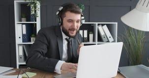 Επιχειρηματίας που έχει τη διασκέδαση ακούοντας και τραγουδώντας τη μουσική στον εργασιακό χώρο απόθεμα βίντεο