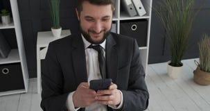 Επιχειρηματίας που έχει τη διασκέδαση που χρησιμοποιεί το κινητό τηλέφωνο στο γραφείο απόθεμα βίντεο