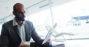 Επιχειρηματίας που έχει τον καφέ διαβάζοντας ένα έγγραφο απόθεμα βίντεο