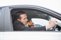 Επιχειρηματίας που έχει τον καφέ και doughnut στο τηλέφωνο Στοκ Εικόνες