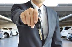 Επιχειρηματίας που δίνει ένα κλειδί αυτοκινήτων - πώληση αυτοκινήτων & έννοια ενοικίου Στοκ εικόνα με δικαίωμα ελεύθερης χρήσης