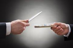 Επιχειρηματίας που δίνει τα χρήματα στο businessperson με το μαχαίρι Στοκ φωτογραφία με δικαίωμα ελεύθερης χρήσης