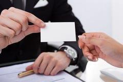 Επιχειρηματίας που δίνει τη επαγγελματική κάρτα στο συνάδελφο Στοκ Εικόνες