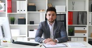 Επιχειρηματίας που ακούει και που παίρνει ματαιωμένος με την τοποθέτηση του κεφαλιού στον πίνακα απόθεμα βίντεο