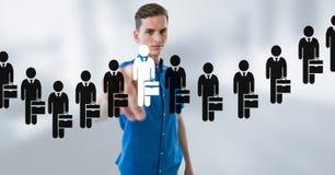 Επιχειρηματίας που αλληλεπιδρά και που επιλέγει ένα πρόσωπο από τα εικονίδια ομάδων ανθρώπων Στοκ Εικόνες