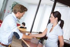 Επιχειρηματίας που αλληλεπιδρά με τον όμορφο ρεσεψιονίστ στο ξενοδοχείο Στοκ Φωτογραφία
