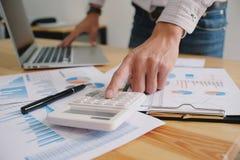 Επιχειρηματίας που αναλύει τα διαγράμματα επένδυσης και που πιέζει τον υπολογιστή Στοκ Εικόνες