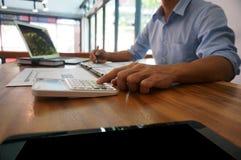 Επιχειρηματίας που αναλύει τα διαγράμματα επένδυσης και που πιέζει τον υπολογιστή Στοκ Φωτογραφίες