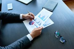 Επιχειρηματίας που αναλύει την έκθεση στατιστικών Στοκ Φωτογραφία