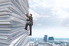 Επιχειρηματίας που αναρριχείται επάνω σε έναν τεράστιο σωρό του εγγράφου Στοκ Φωτογραφία