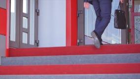 Επιχειρηματίας που αναρριχείται επάνω στα σκαλοπάτια στο κτήριο γραφείων φιλμ μικρού μήκους
