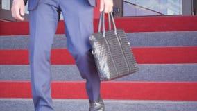 Επιχειρηματίας που αναρριχείται επάνω στα σκαλοπάτια στο κτήριο γραφείων απόθεμα βίντεο