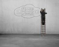 Επιχειρηματίας που αναρριχείται και που επισύρει την προσοχή app στο εικονίδιο στο συμπαγή τοίχο Στοκ Εικόνες