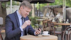 Επιχειρηματίας που ανατρέπεται από την απώλεια σε Smartphone, που κάθεται στον υπαίθριο καφέ απόθεμα βίντεο
