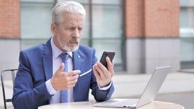 Επιχειρηματίας που ανατρέπεται παλαιός από την απώλεια χρησιμοποιώντας Smartphone απόθεμα βίντεο