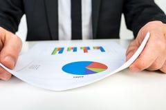 Επιχειρηματίας που αναλύει ένα σύνολο γραφικών παραστάσεων φραγμών και πιτών Στοκ Εικόνες