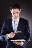 Επιχειρηματίας που αναλύει τα έγγραφα με την ενίσχυση - γυαλί Στοκ εικόνα με δικαίωμα ελεύθερης χρήσης