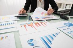 Επιχειρηματίας που αναλύει την έκθεση σχετικά με το διάγραμμα Στοκ εικόνες με δικαίωμα ελεύθερης χρήσης
