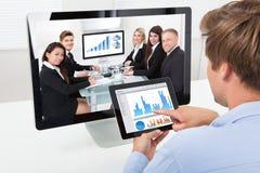 Επιχειρηματίας που αναλύει τις γραφικές παραστάσεις ενώ τηλεοπτική σύσκεψη Στοκ εικόνα με δικαίωμα ελεύθερης χρήσης