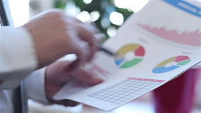 Επιχειρηματίας που αναλύει τις εισοδηματικές γραφικές παραστάσεις απόθεμα βίντεο