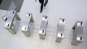 Επιχειρηματίας που ανιχνεύει τις κάρτες τους στην πύλη περιστροφικών πυλών απόθεμα βίντεο