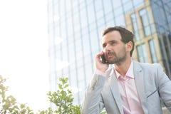 Επιχειρηματίας που απαντά στο κινητό τηλέφωνο έξω από το κτίριο γραφείων Στοκ Φωτογραφίες