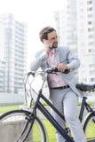 Επιχειρηματίας που απαντά στο κινητό τηλέφωνο στεμένος με το ποδήλατο υπαίθρια Στοκ Φωτογραφίες