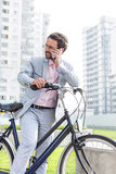 Επιχειρηματίας που απαντά στο κινητό τηλέφωνο στεμένος με το ποδήλατο υπαίθρια Στοκ Εικόνες