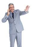 Επιχειρηματίας που απαντά στο τηλέφωνο και τον κυματισμό Στοκ Εικόνες