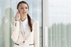 Επιχειρηματίας που απαντά στο τηλέφωνο κυττάρων από την πόρτα γυαλιού Στοκ φωτογραφίες με δικαίωμα ελεύθερης χρήσης