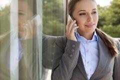 Επιχειρηματίας που απαντά στο τηλέφωνο κυττάρων από την πόρτα γυαλιού Στοκ Εικόνα