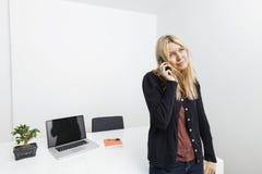 Επιχειρηματίας που απαντά στο τηλέφωνο κυττάρων στην αρχή Στοκ φωτογραφία με δικαίωμα ελεύθερης χρήσης