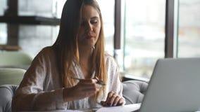 Επιχειρηματίας που απασχολείται με το lap-top και τους ελέγχους στα έγγραφα στον καφέ απόθεμα βίντεο