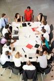 Επιχειρηματίας που απευθύνεται στη συνεδρίαση γύρω από τον πίνακα αιθουσών συνεδριάσεων Στοκ φωτογραφία με δικαίωμα ελεύθερης χρήσης
