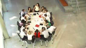 Επιχειρηματίας που απευθύνεται στη συνεδρίαση γύρω από τον πίνακα αιθουσών συνεδριάσεων απόθεμα βίντεο