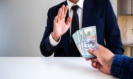 Επιχειρηματίας που αρνείται τα χρήματα που προσφέρονται από το συνεργάτη του στοκ εικόνα