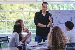 Επιχειρηματίας που αυξάνει το χέρι για να υποβάλει την ερώτηση στο άτομο μπροστά από με στοκ φωτογραφία με δικαίωμα ελεύθερης χρήσης