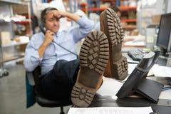 Επιχειρηματίας που βάζει τα πόδια επάνω στο γραφείο στην αποθήκη εμπορευμάτων Στοκ Φωτογραφία