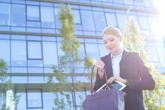 Επιχειρηματίας που βάζει την ψηφιακή ταμπλέτα στο πορτοφόλι την ηλιόλουστη ημέρα Στοκ Φωτογραφία