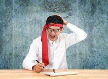 Επιχειρηματίας που γράφει με το σημειωματάριο στο γραφείο Ασιατικό θόριο επιχειρηματιών Στοκ Φωτογραφία