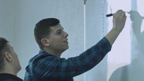 Επιχειρηματίας που γράφει μια λειτουργία και που βάζει τις ιδέες του σχετικά με το λευκό πίνακα κατά τη διάρκεια μιας παρουσίασης απόθεμα βίντεο