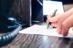 Επιχειρηματίας που γράφει σε επιχειρησιακό χαρτί στην αρχή Στοκ Φωτογραφία