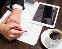 Επιχειρηματίας που γράφει σε χαρτί δίπλα στην ταμπλέτα, καφές, τηλέφωνο κυττάρων Στοκ Εικόνα