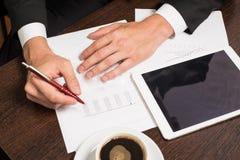 Επιχειρηματίας που γράφει σε χαρτί δίπλα στην ταμπλέτα, καφές, τηλέφωνο κυττάρων Στοκ Εικόνες